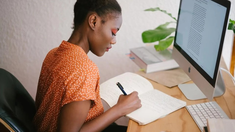 Processo seletivo Prefeitura de Caibi - SC: imagem de uma mulher de cor de pele preta escrevendo em um caderno. Na mesa há um computador e livros.