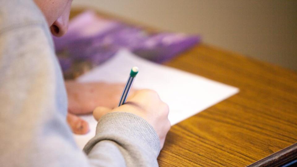 Processo seletivo Prefeitura de Campina Verde: pessoa sentada em carteira de escola escrevendo num papel