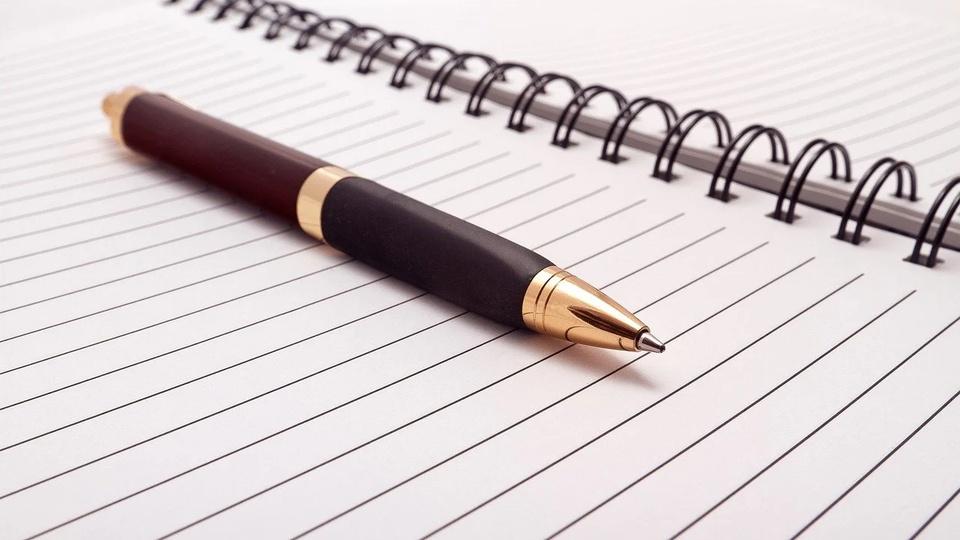 Processo seletivo Prefeitura de Caroebe - RR:  a imagem mostra caneta sobre caderno aberto com páginas em branco