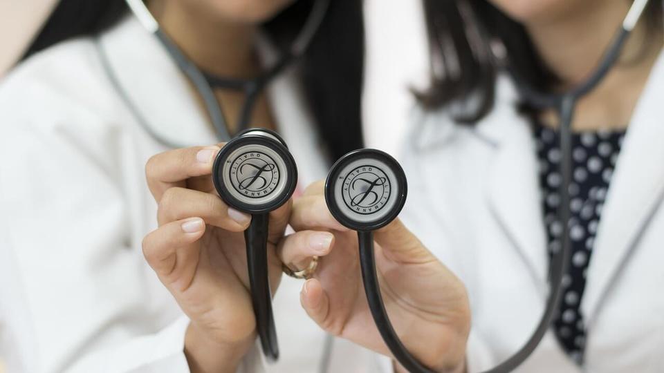 processo seletivo prefeitura de casinhas: duas profissionais da saúde vestindo jalecos brancos e apontando estetoscópios para frente como se fizessem um exame