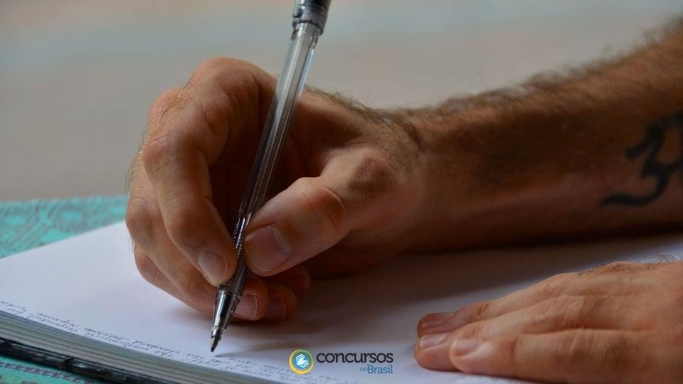 Processo seletivo Prefeitura de Catas Altas - MG: a foto mostra uma mão de homem branco segurando uma caneta e fazendo anotações em um caderno