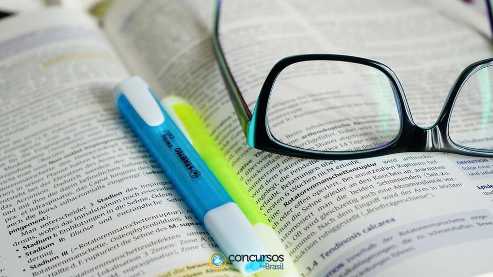 Processo seletivo Prefeitura de Chalé - MG: a imagem mostra parte de um óculos, duas canetas marcadoras de texto (uma azul e outra verde) em cima de um livro aberto