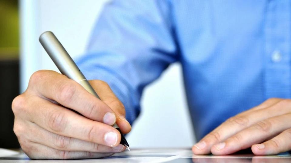Processo seletivo Prefeitura de Chapada dos Guimarães: a imagem mostra um home de camisa social azul marinho claro, segurando uma caneta e escrevendo em um papel