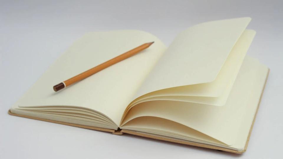 Processo seletivo Prefeitura de Cláudia - MT: a imagem mostra caderno aberto e um lápis