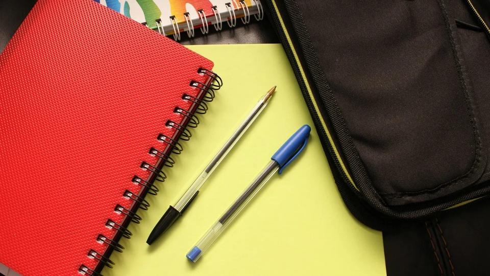 Processo seletivo Prefeitura de Cordilheira Alta: a foto mostra três cadernos de formatos diferentes, um de capa vermelha, outro de capa colorida e outro aberto com folha amarela e duas canetas sobre superfície plana, há também uma bolsa preta,