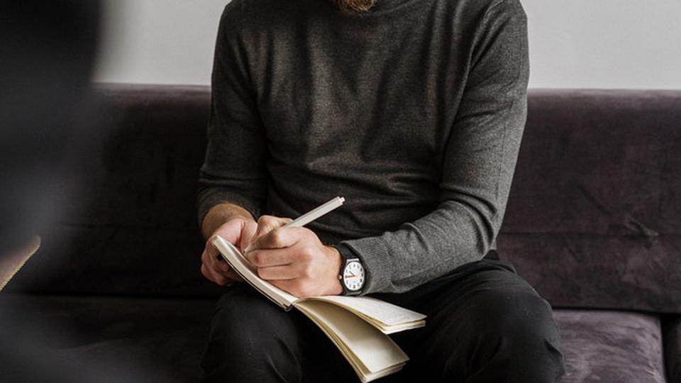 Prefeitura de Dom Joaquim - SC: homem de blusa cinza e calça preta sentado no sofá anota o que o outro está falando