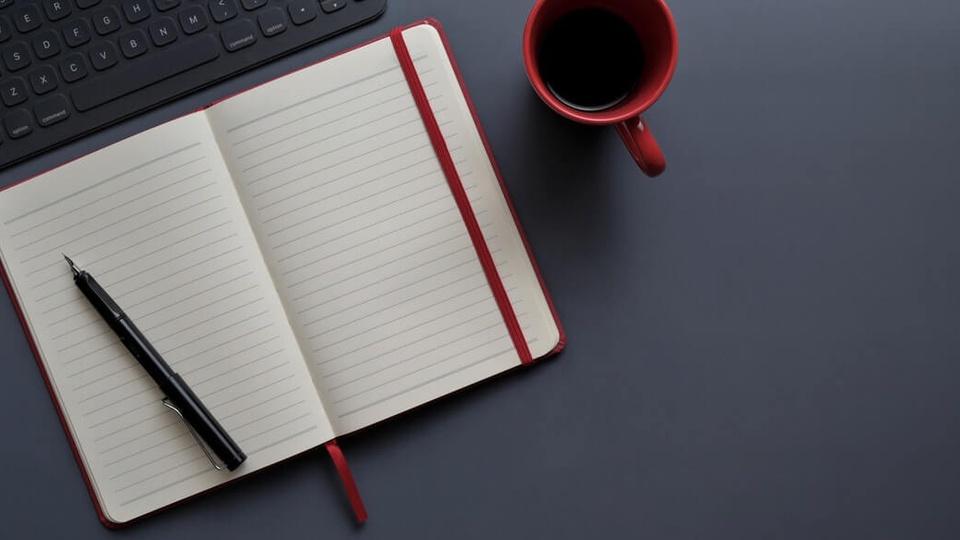 processo seletivo Prefeitura de Gongogi: a imagem mostra caderno aberto com caneta por cima ao lado de xícara de café