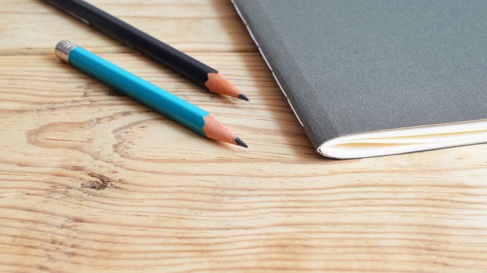 Processo seletivo Prefeitura de Guaçuí - ES: a imagem mostra dois lápis sobre uma superficie de madeira, um é azul e outro é preto, além de um caderno sem espiral de capa cinza