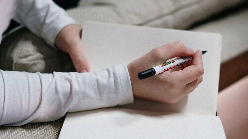 Processo seletivo Prefeitura de Guaimbê - SP: a imagem mostra pessoa segurando caneta anotando algo em caderno