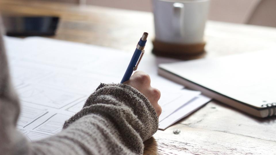 Processo seletivo Prefeitura de Guaraciaba - SC: pessoa fazendo anotação em papel com xícara de café na frente
