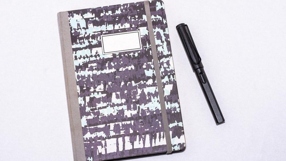 processo seletivo Prefeitura de Indaial: a imagem mostra caderno de capa nas cores preto e branco com caneta com caneta ao lado