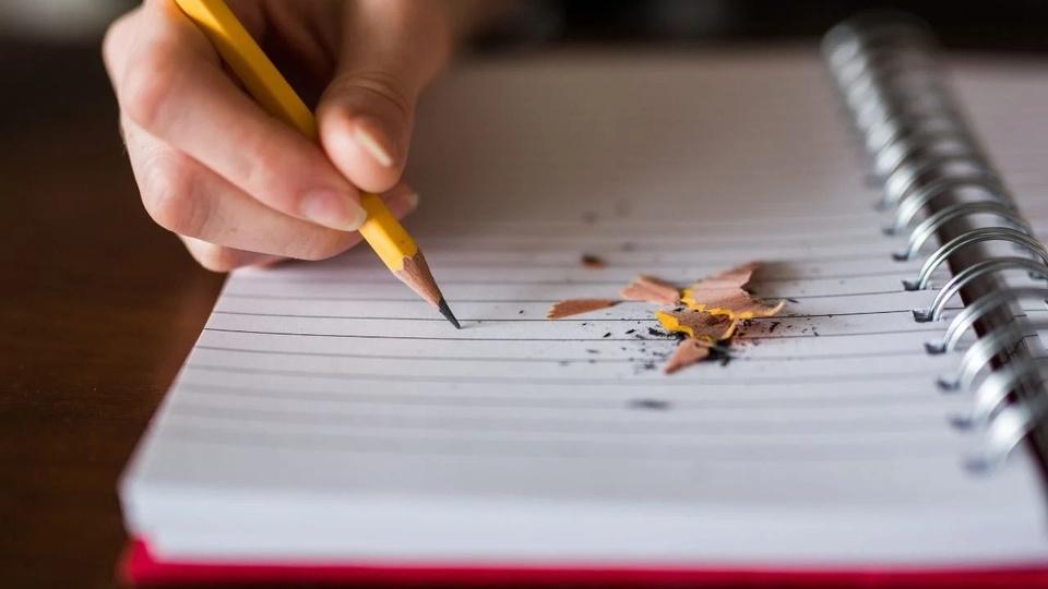 Processo seletivo Prefeitura de Isaías Coelho - PI: a imagem mostra uma mão com um lápis anotando em um caderno, há restos da raspagem do lápis em cima do caderno, provenientes do apontamento com lapiseira de lâmina