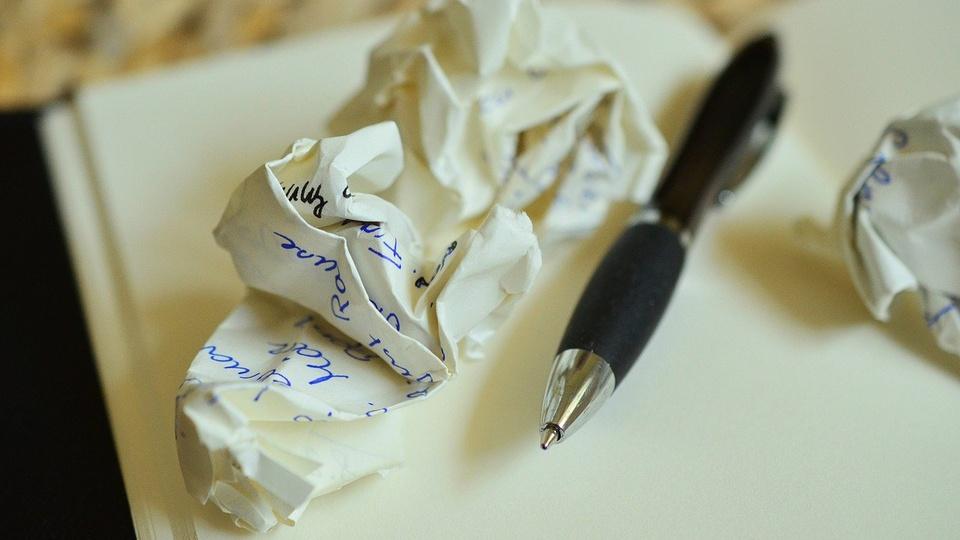 processo seletivo prefeitura de itaqui: a imagem mostra caderno aberto com caneta e folhas de papel amassado por cima
