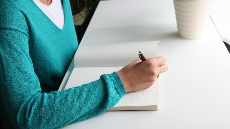 Processo seletivo PRefeitura de Itarana ES: a imagem mostra pessoa escrevendo algo em papel sentada em escrivaninha