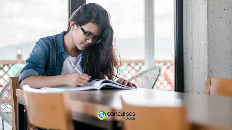 Processo seletivo Prefeitura de Japurá - AM: a imagem monstra uma jovem estudante, de cabelos negros e longos, usando óculos, sentada, estudando, fazendo anotações em um livro