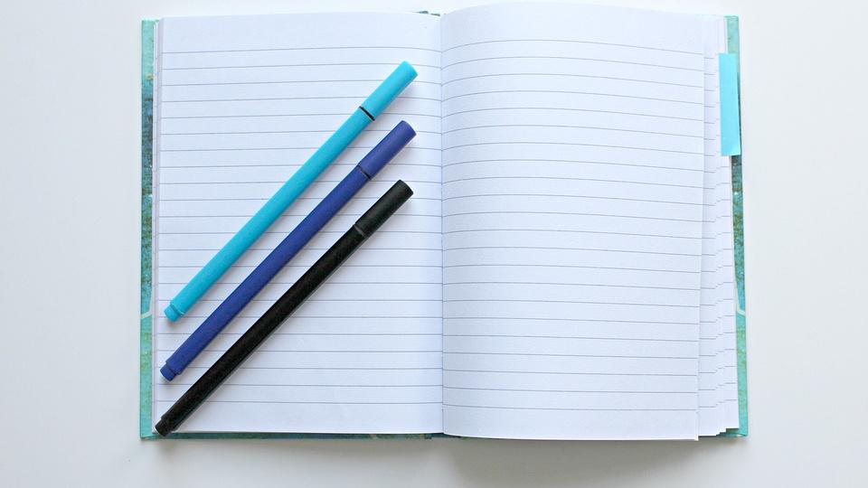 Processo seletivo Prefeitura de Laguna Carapã: a imagem mostra caderno aberto com três canetas azuis em cima