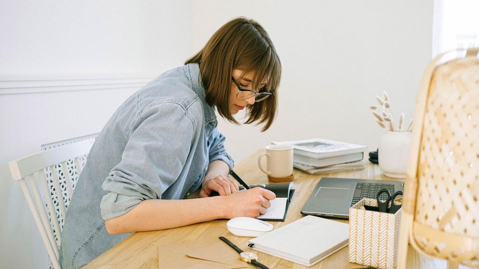 Prefeitura de Luz: mulher de óculos escrevendo em um caderno. Na mesa há vários objetos, como xícara, vaso, livros, laptop, relógio, agenda e mouse.