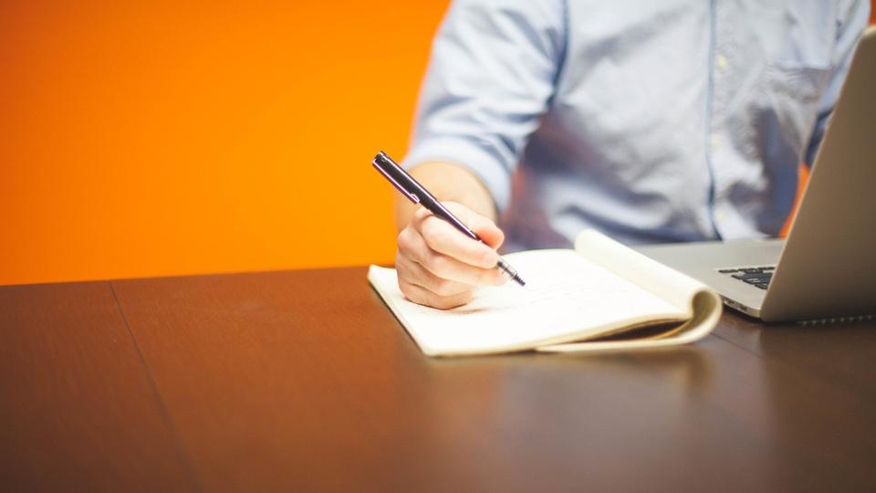 Processo seletivo Prefeitura de Major Gercino - SC: homem mexendo em notebook e escrevendo em folha de papel