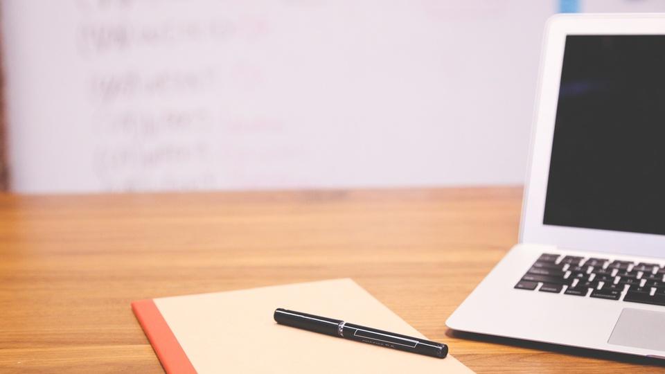 Processo seletivo Prefeitura de Nova Resende - MG: caneta, folha de papel e notebook sob mesa