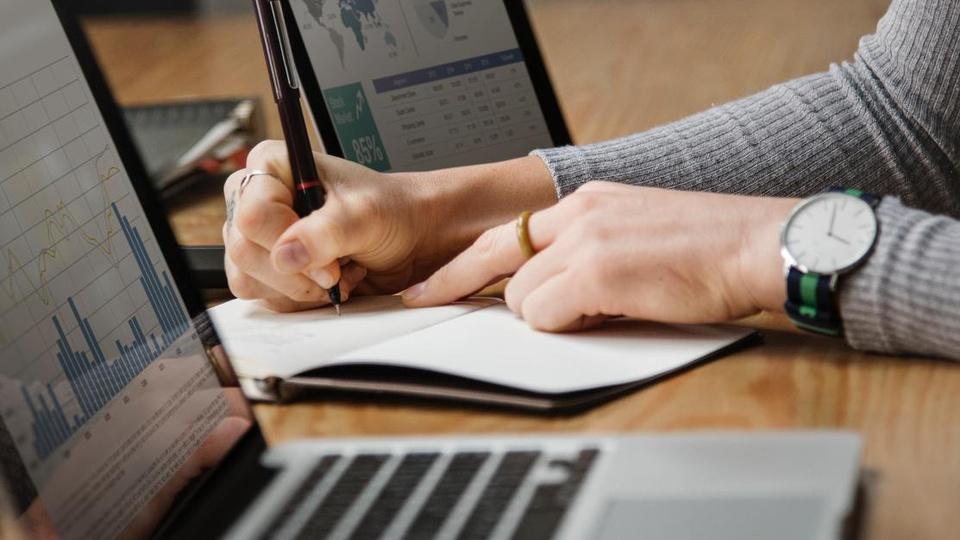Processo seletivo Prefeitura de Nova Santa Helena - MT: a imagem mostra notebook sob mesa; pessoa escrevendo em folha de papel