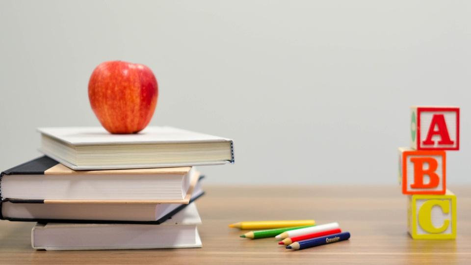 Processo seletivo Prefeitura de Paial - SC: mesa de professor com livros, dados com letras do alfabeto e maçã