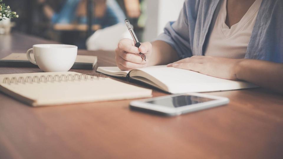 Processo seletivo Prefeitura de Palmeira: Pessoa sentada a mesa, estudando com duas agendas abertas, na mão direita uma caneta, ao lado direito uma xícara e do lado esquerdo uma celular.
