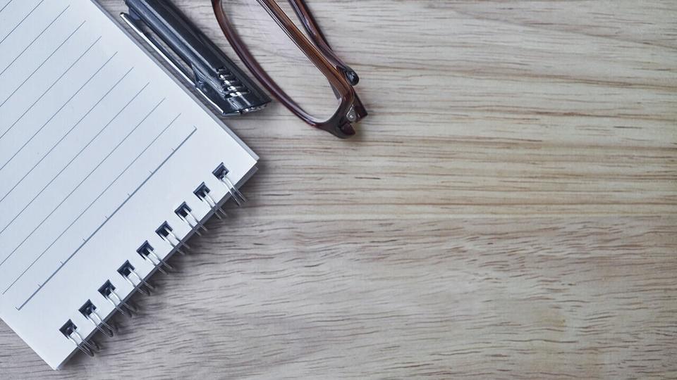 Processo seletivo Prefeitura de Paraíso - SC: bloco de anotação ao lado de caneta e óculos
