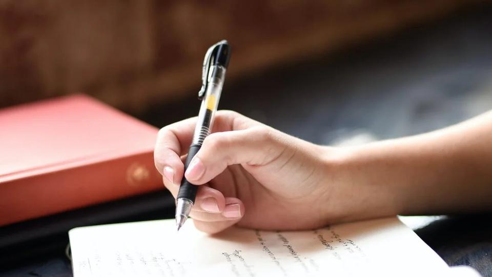 Processo seletivo Prefeitura de Portalegre - RN: enquadramento em mão escrevendo em caderno