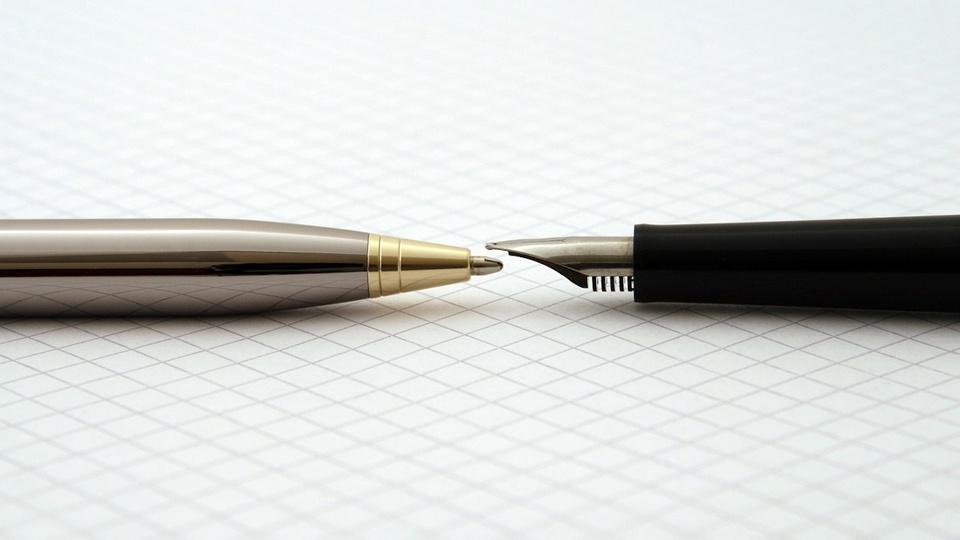 Processo seletivo Prefeitura de Praia Grande - SC: a imagem mostra duas canetas de luxo (a da direita é uma caneta tinteiro bico de pena), uma com a ponta virada para a outra