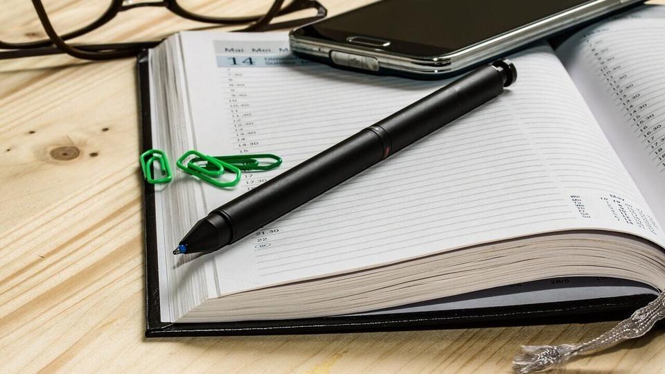 Processo seletivo Prefeitura de Quebrangulo - AL: a imagem mostra caderno aberto com lápis, clipe e celular em cima. Atrás há um óculos.