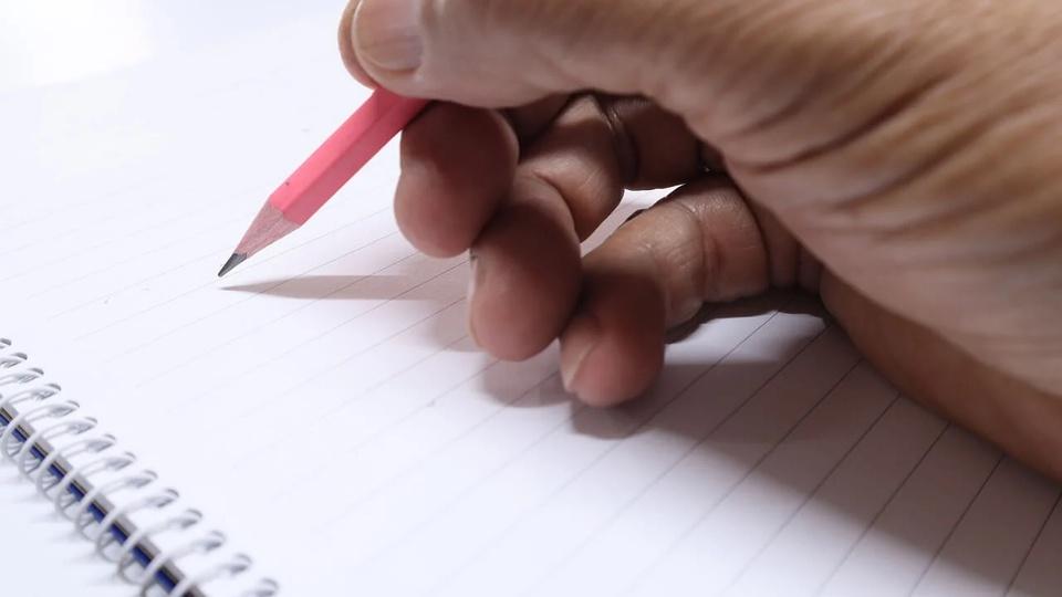 Processo seletivo Prefeitura de Querência - MT: a imagem mostra mão segurando lápis escrevendo em caderno