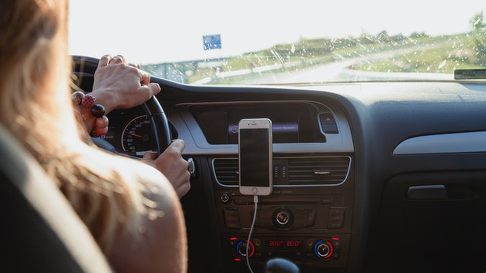 Prefeitura de Quevedos: imagem de uma mulher dirigindo um automóvel. Na foto é possível ver o painel do carro e um celular sobre ele.