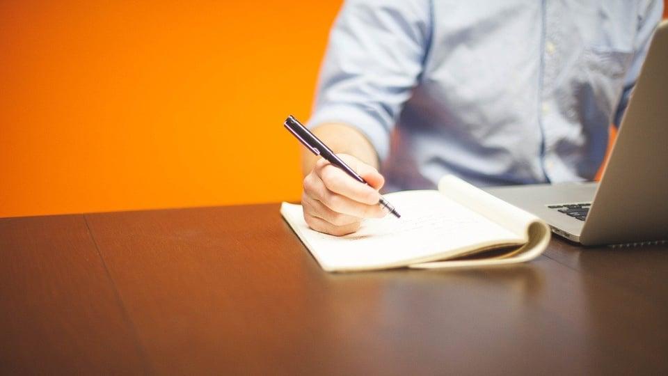 Processo seletivo Prefeitura de Raposa - MA: homem escreve em folha de papel e mexe no notebook