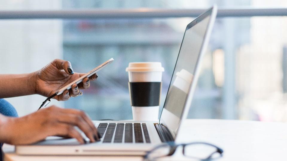 Processo seletivo Prefeitura de Realeza - PR: enquadramento em pessoa segurando celular com uma mão enquanto digita no notebook com a outra mão