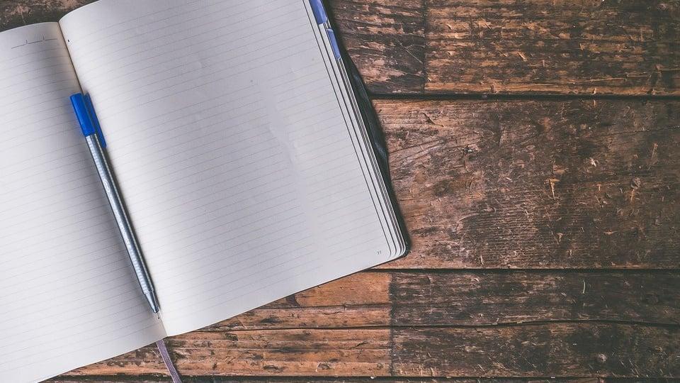 processo seletivo prefeitura de rio das antas: a imagem mostra caderno aberto sobre mesa de madeira com caneta em cima