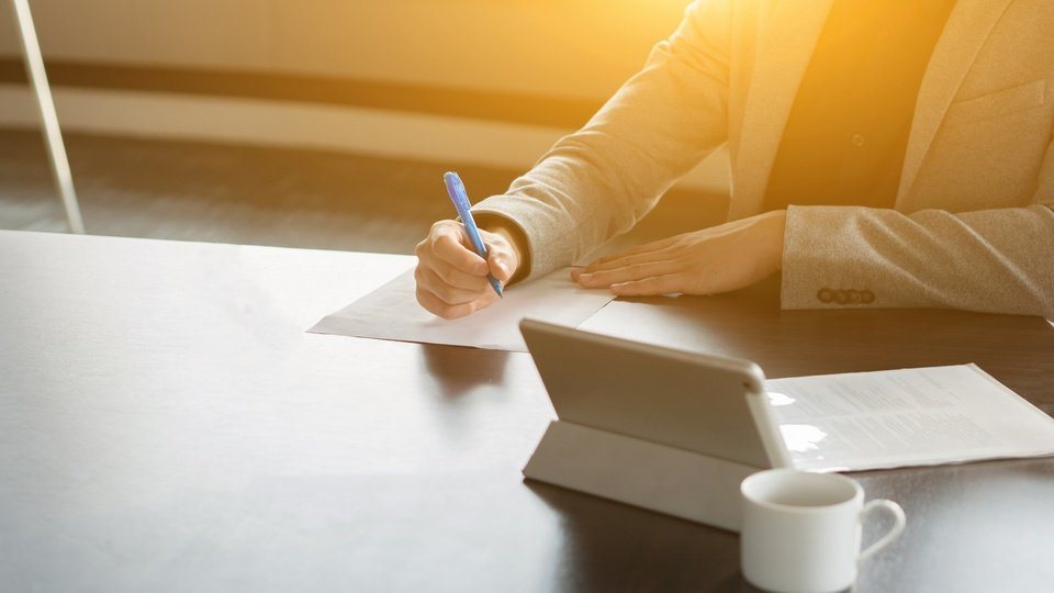 Processo seletivo Prefeitura de Roseira - SP: folhas sob mesa; pessoa escreve em uma folha de papel