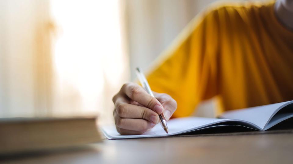 Processo seletivo Prefeitura de Santa Carmem - MT: uma pessoa fazendo anotações em um caderno