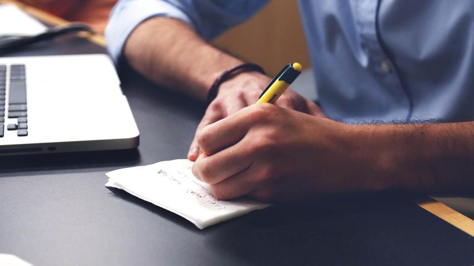 Processo seletivo Prefeitura de São Bento do Sul - SC: notebook e folha de papel sob mesa; homem escrevendo em folha de papel