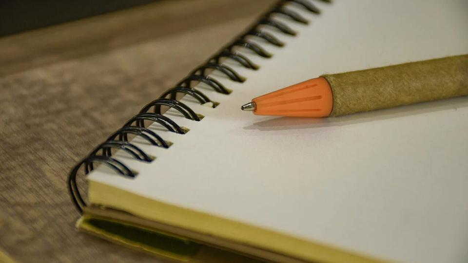 Processo seletivo Prefeitura de São João do Sul - SC: a imagem mostra caderno aberto e um lápis em um cenário amarelado, como a cor do caderno e do lápis