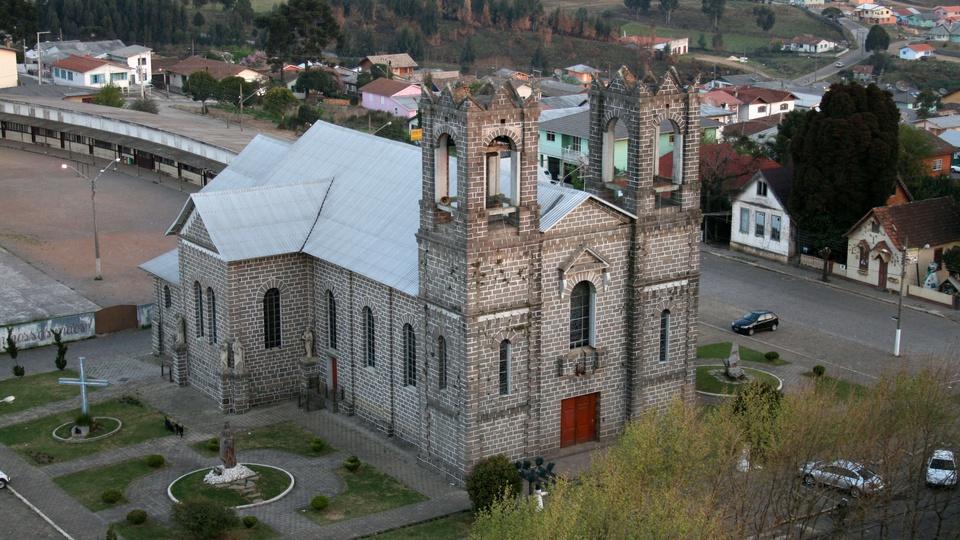Processo seletivo Prefeitura de São Joaquim SC:  foto da igreja matriz de São Joaquim, Santa Catarina, alguns carros, pessoas, com destaque para a arquitetura da igreja