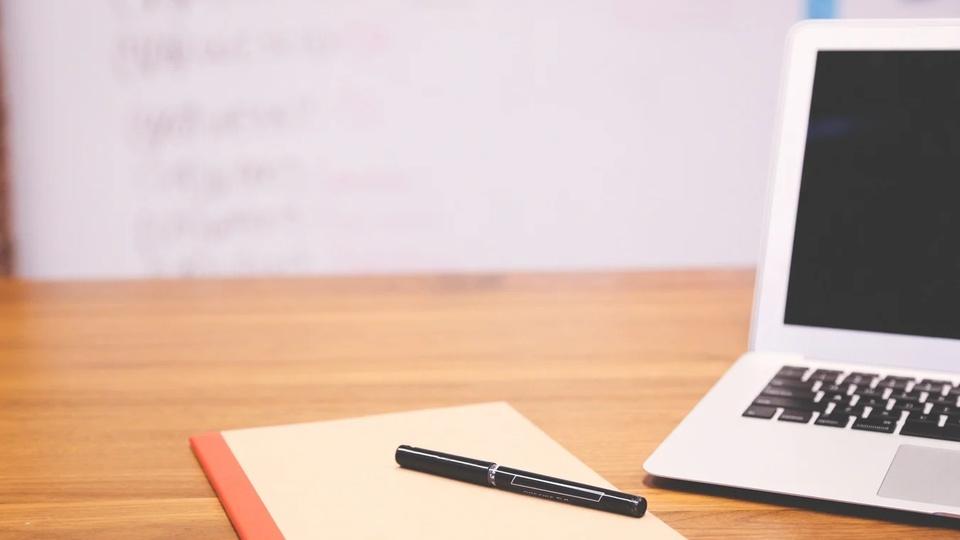 Processo seletivo Prefeitura de São Martinho - SC: #PraCegoVer mesa com notebook, caderno e caneta