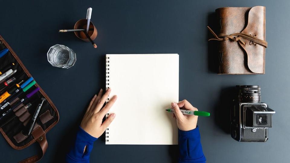 Processo seletivo Prefeitura de São Pedro do Turvo - SP: a imagem mostra pessoa fazendo anotação em caderno, a cor da mesa é escura