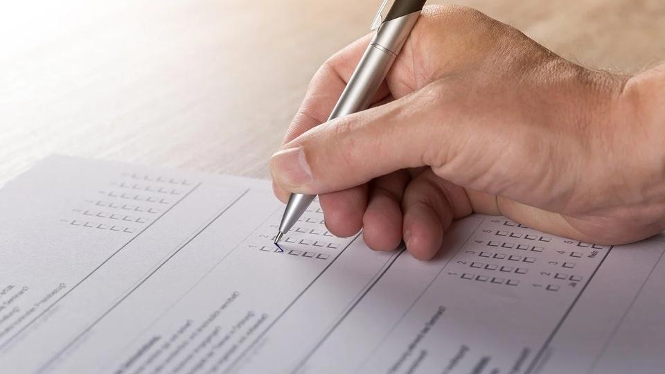 Processo seletivo Prefeitura de Sapezal: a imagem mostra pessoa segurando caneta e assinalando questão de prova