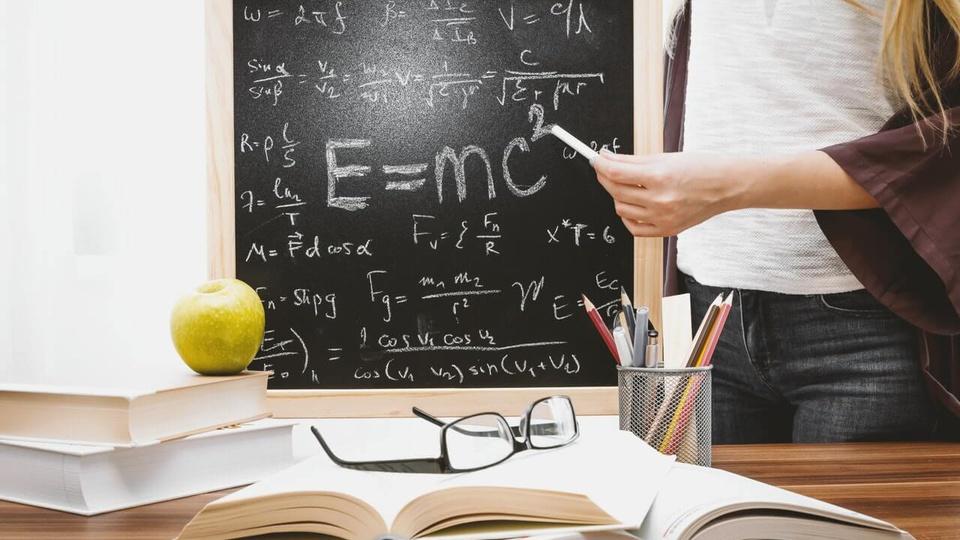 processo seletivo Prefeitura de Saquarema: a imagem mostra professor segurando quadro negro com uma mão e giz com a outra apontando para o quadro. Na sua frente há uma mesa com livros, uma maçã verde e um óculos