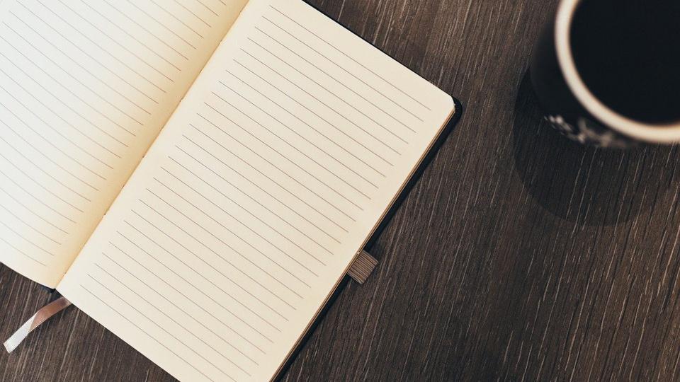 processo seletivo prefeitura de sonora: a imagem mostra caderno aberto ao lado de caneca de café
