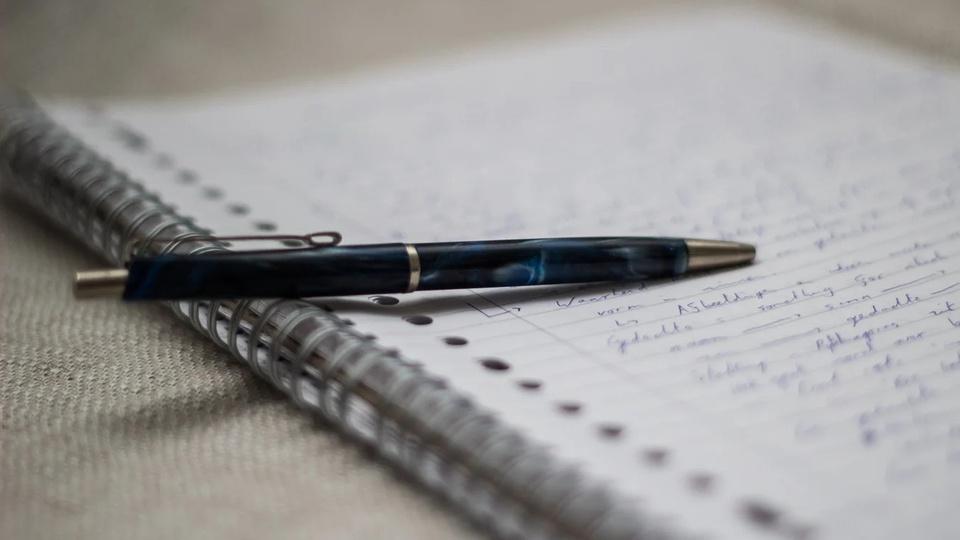 Processo seletivo Prefeitura de Taciba - SP: foco em caderno e caneta sob superfície