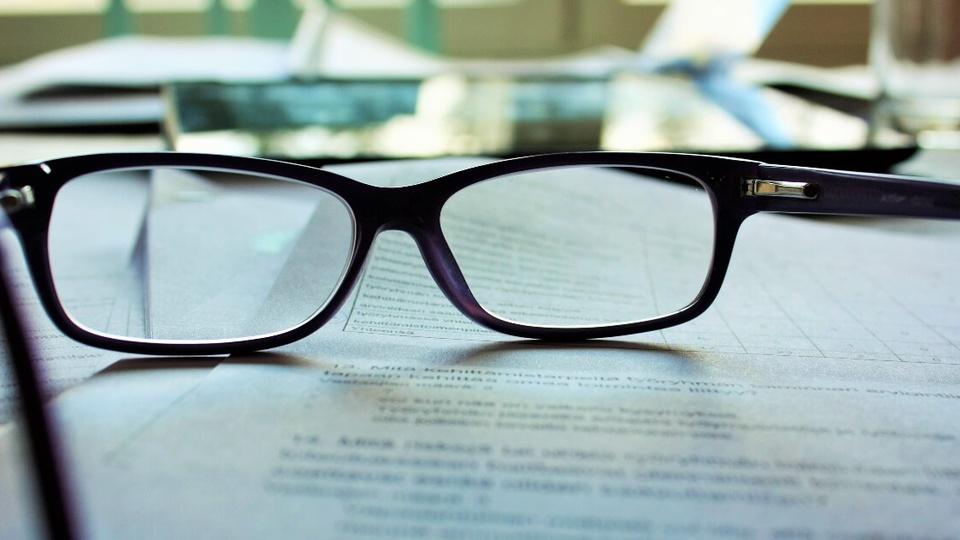Processo seletivo Prefeitura de Teixeiras - MG: óculos sobre papéis