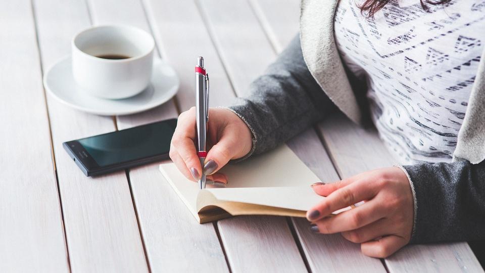 Processo seletivo Prefeitura de Trindade - GO 2021: a foto mostra as mãos de uma mulher sobre uma mesa, há um celular preto por perto, e uma xícara branca contendo café preto ao lado. Ela faz anotações em um pequeno caderno