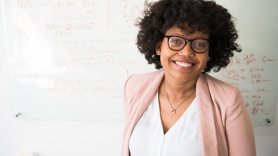 Prefeitura de Trombudo Central: foco em mulher de óculos, sorrindo; ao fundo quadro branco de escola
