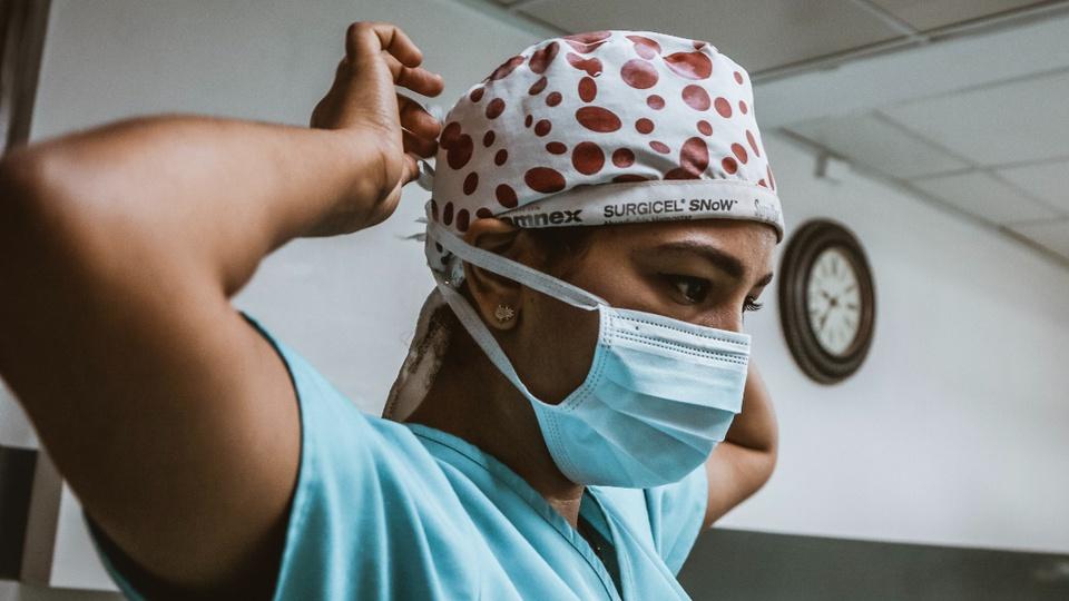 Processo seletivo Prefeitura de Turvo - foto mostra profissional da saúde trajando uniforme cirúrgico e vestindo máscara descartável
